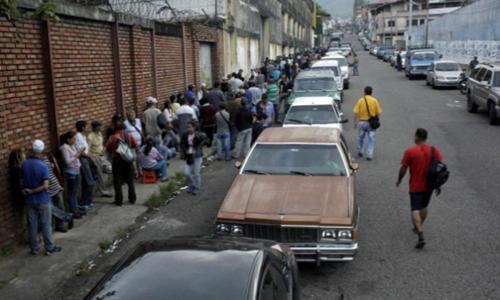 Dòngngười xếp hàng trước cửa siêu thị cạnh dãyôtô chờ mua xăng tại San Cristobal. Ảnh: Reuters