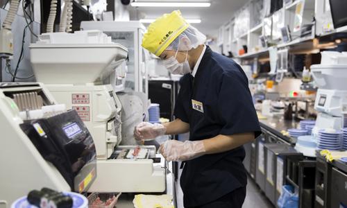 Nhân viên Kura chế biến sushi trong bếp. Ảnh: Bloomberg
