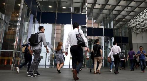 Người làm việc đi đến văn phòng tại khu vực trung tâm Singapore. Ảnh: Bloomberg