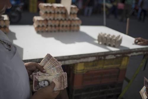 Một công nhân đếm tiền tại một quầy trứng ở Caracas (Venezuela). Ảnh: Bloomberg