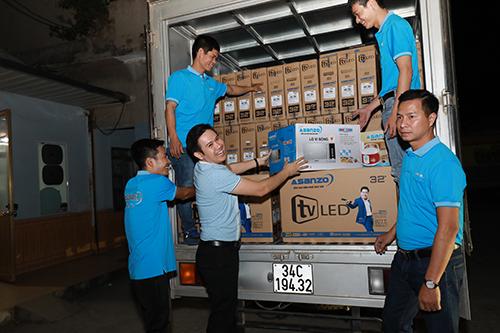 Chủ tịch Asanzo Phạm Văn Tam (thứ hai từ trái qua) trong chuyến đi về quê thủ môn Bùi Tiến Dũng tặng tivi cho các hộ nghèo tại đây. Ảnh: Phương Nguyên
