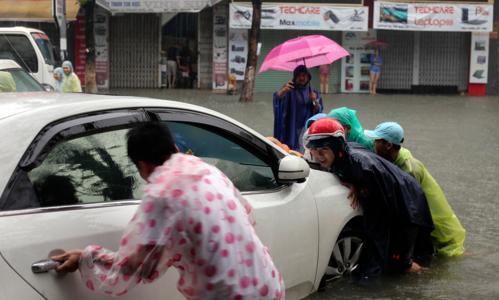 Hàng loạt ôtô, xe máy bị hư hỏng khi phố biến thành sông. Ảnh: Nguyễn Đông.