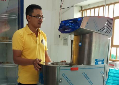 Anh Hồ Sĩ Bảo bên chiếc máy điều chỉnh nhiệt độ chocolate để tạo tính kết tinh trước khi đổ khuôn.