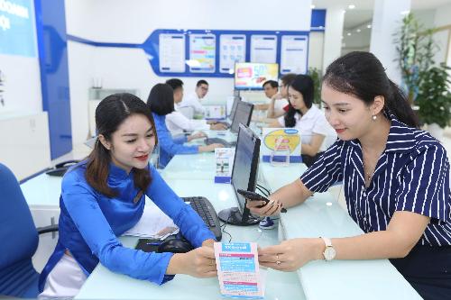 Nhân viên một nhà mạng đang hướng dẫn khách hàng thực hiện dịch vụ tại điểm giao dịch.