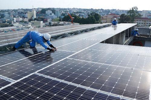 Công nhân kiểm tra lắp đặt điện mặt trời áp mái. Ảnh: EVNSPC
