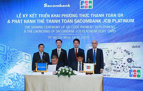 Ông Phạm Đức Duy - Phó giám đốc phụ trách Trung Tâm Thẻ (bên trái) và ông Ryuji Ichikawa  Phó đại diện JCB International tại Thành phố Hồ Chí Minh ký kết triển khai phương thức thanh toán QR dưới sự chứng kiến của Lãnh đạo hai bên.