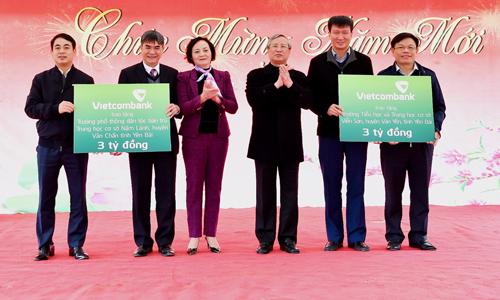 Đ/c Nghiêm Xuân Thành - Chủ tịch HĐQT Vietcombank (ngoài cùng bên trái) và đ/c Đào Minh Tuấn  Phó Tổng Giám đốc, Chủ tịch Công đoàn Vietcombank (ngoài cùng bên phải) trao tượng trưng số tiền 6 tỷ đồng ủng hộ của Vietcombank để xây dựng 2 trường học tại huyện Văn Chấn và Văn Yên trước sự chứng kiến của đ/c Trần Quốc Vượng - Ủy viên Bộ Chính trị, Thường trực Ban Bí thư (thứ 3 từ phải sang) và đ/c Phạm Thị Thanh Trà - Ủy viên BCH Trung ương Đảng, Bí thư Tỉnh ủy, Chủ tịch HĐND tỉnh Yên Bái (thứ 3 từ trái sang)