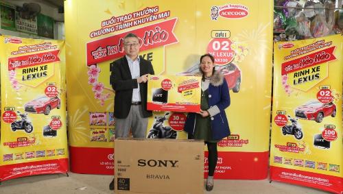 Ông Majima Fumihiro - Giám đốc Acecook Việt Nam chi nhánh Hà Nội trao giải ba cho chị Nguyễn Thị Na tại chợ Vác, Hà Nội ngày 18/1.