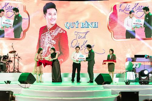 Doanh nhânNguyễn Ngọc Tiền và nghệ sĩ Quý Bình trao tặng các phần quàcho huyện Hóc Môn.
