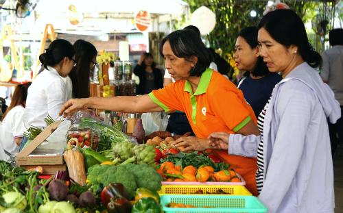 Người tiêu dùng đang chọn mua rau củ tại một phiên chợ thực phẩm sạch. Ảnh: Viễn Thông