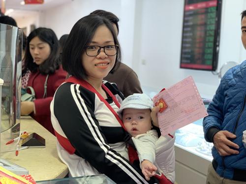 Em bé theo chân mẹ đi mua vàng cầu may tại Trung tâm DOJI 37B Trần Nhân Tông, quận Hai Bà Trưng, Hà Nội.