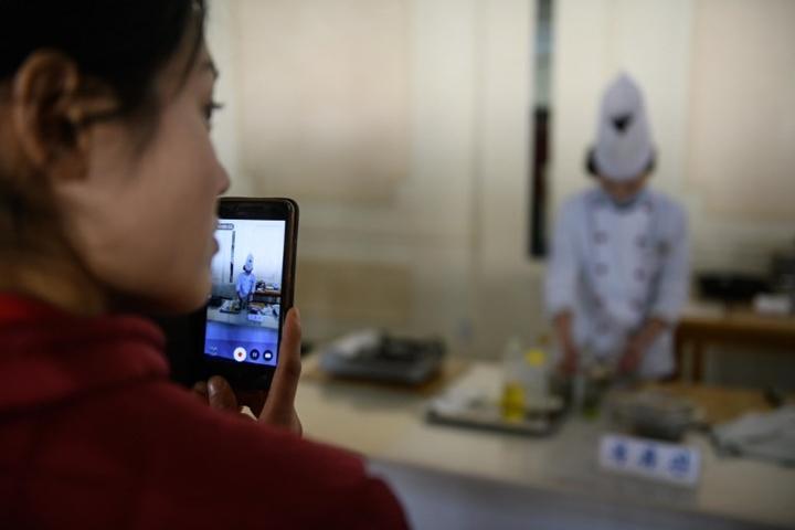 Người dân dùng smartphone trong một cuộc thi nấu ăn ở Triều Tiên. Ảnh: AFP