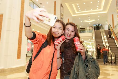 Khách hàng thích thú khi nhận lon Coca-Cola đặc biệt tại máy kết nối hòa bình.