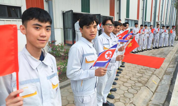 Các kỹ sư Vinfast vẫy cờ đón đoàn Triều Tiên trước nhà xưởng. Ảnh: Hữu Khoa