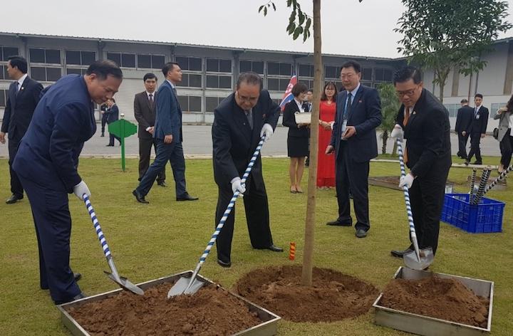 Ông Ri Su Yong (giữa), Phó chủ tịch Đảng lao động Triều Tiên trồng cây lưu niệm trong khuôn viên nhà máy.