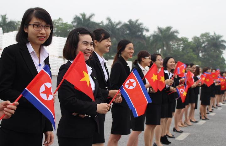 Nhân viên cầm cờ Việt Nam, Triều Tiên vẫy chào mừng đoàn lãnh đạo Triều Tiên.