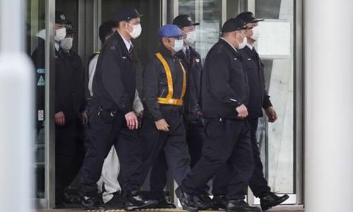 Carlos Ghosn, người đeo miếng dánphản quang, đội mũ xanh dương,bước ra khỏi phòng giam chiều nay. Ảnh: Bloomberg