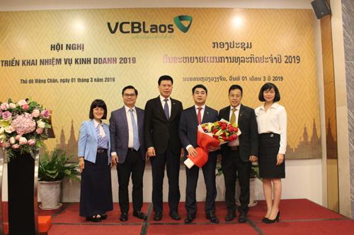 Ông Phạm Mạnh Thắng - Phó tổng giám đốc Vietcombank, Chủ tịch HĐQT Vietcombank Lào (thứ 3 từ trái sang) tặng hoa cho ông Nghiêm Xuân Thành - Chủ tịch HĐQT Vietcombank (thứ 3 từ phải sang).