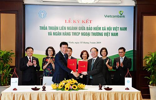 Đại diện BHXH Việt Nam, ông Nguyễn Đình Khương – Phó Tổng Giám đốc (hàng đầu, bên phải) cùng đại diện Vietcombank, ông Phạm Mạnh Thắng – Phó Tổng Giám đốc ký kết thoả thuận liên ngành