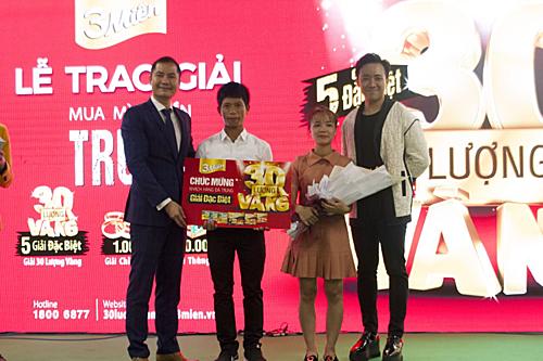 Nghệ sĩ Trấn Thành cùng ông Nguyễn Thế Anh - Phó tổng giám đốc Uniben (bìa trái) trao giải thưởng 30 lượng vàng đầu tiền cho gia đình anh Đặng Văn Mười.