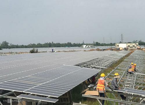 Công nhân hối hả lắp những tấm pin điện mặt trời cuối cùng tại một dự án điện mặt trời ở Long An. Ảnh: H.T