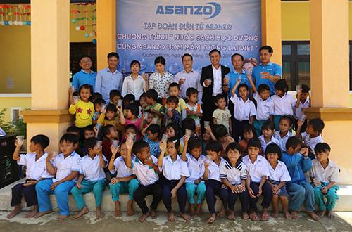 Nhân viên tập đoàn Asanzo, giáo viên và học sinh điểm trường Khe Chữ cùng thưởng thức nước máy vừa lắp xong. Ảnh: Đắc Thành.