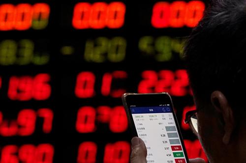 Nhà đầu tư tại một công ty môi giới chứng khoán ở Thượng Hải. Ảnh: Reuters
