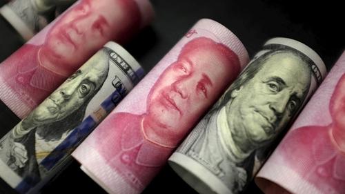 Đồng NDT của Trung Quốc và USD của Mỹ. Ảnh: Reuters