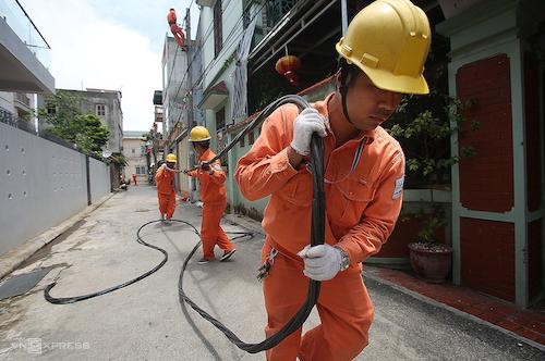 Công nhân điện lực Hà Nội kéo dây sửa chữa lưới điện. Ảnh: Ngọc Thành