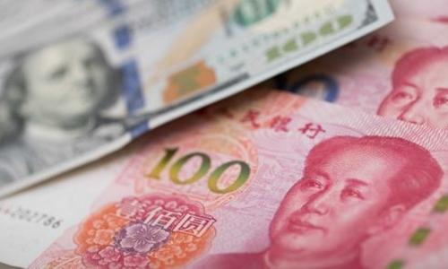Đồng 100 USD của Mỹ và 100 NDT của Trung Quốc. Ảnh: AFP