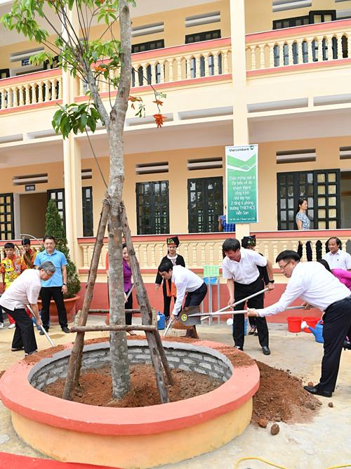 [Caption] Các đại biểu tham gia trồng cây trong khuôn viên nhà trường.