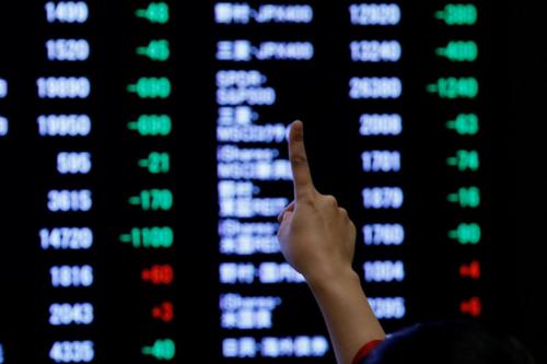 Một nhà đầu tư giơ ngón tay thể hiện sự kỳ vọng với chứng khoán Nhật Bản năm nay. Ảnh: Reuters