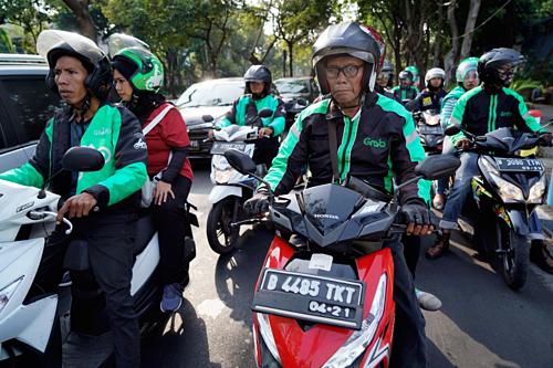 Tài xế Go-Jek và Grab cùng đồng phục áo xanh đen trên đường phố Jakarta. Ảnh: Dimas Ardian