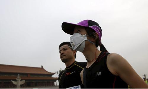 Runner phải đeo khẩu trang vì ô nhiễm không khí ở Bắc Kinh. Ảnh: Reuters