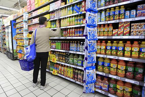 Một người mua đang chọn đồ uống trong siêu thị ở Thượng Hải. Ảnh: Reuters