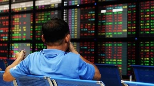 Nhà đầu tư theo dõi bảng điện tử tại một công ty chứng khoán Hà Nội. Ảnh: AFP.