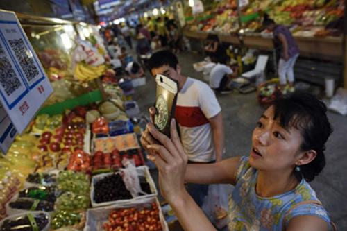 Một khách hàng Trung Quốc đang quét mã QR để thanh toán. Ảnh: VCG