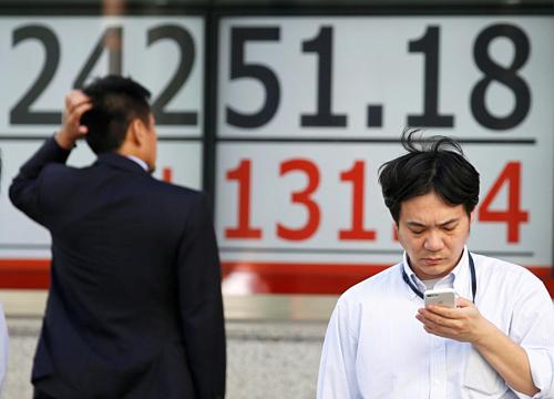 Một người đàn ông xem bảng điện tử bên ngoài một công ty môi giới chứng khoán ở Tokyo. Ảnh: Reuters