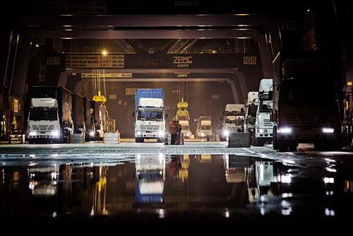 Xe tải chờ nhận hàng ban đêm tại một cảng ở Hạ Môn, Trung Quốc. Ảnh: Bloomberg