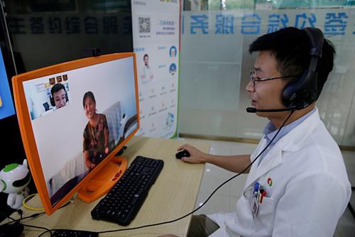 Bác sĩ của Trung tâm Y tế Zhuojing (Sơn Đông) trò chuyện cùng người già. Ảnh: Reuters