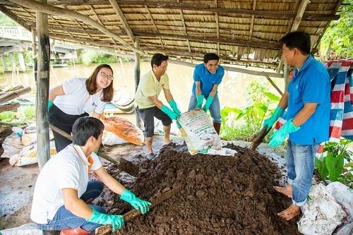 Tình nguyện viên cùng người dân địa phương thu gom rơm rạ ủ phân hữu cơ.