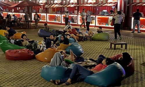 Khách hàng ăn uống trước hội chợ ẩm thực của GoFood tại sân vận động Bung Karno. Ảnh: Bloomberg
