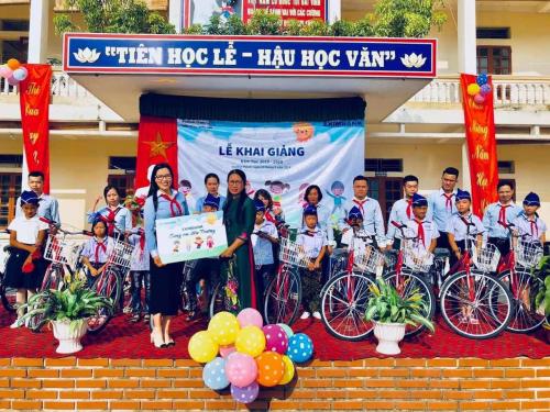 Bà Trịnh Thị Hải Yến - Trưởng Văn phòng Đại diện Eximbank tại Hà Nội (đeo khăn quàng đứng bên trái) trao tặng 10 chiếc xe đạp cho bà Vũ Thị Ngọc Hoa - Hiệu trưởng Trường Tiểu học Trường Thành (người mặt áo dài đứng bên