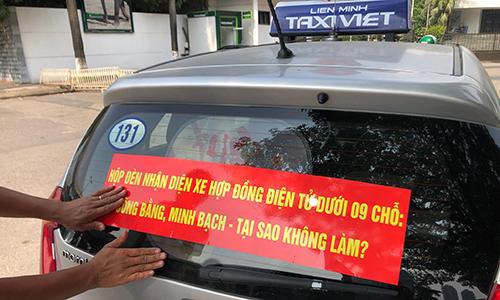 Chiều hãng taxi truyền thống lại dán khẩu hiệu yêu cầu taxi công nghệ gắn mào. Ảnh: Anh Tú
