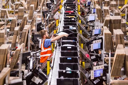 Nhân viên làm việc trong một trung tâm hoàn thiện đơn hàng của Amazon. Ảnh: Bloomberg