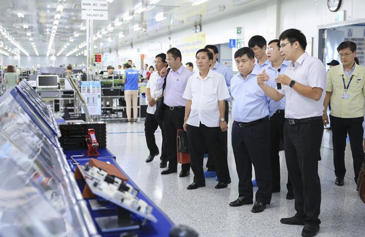 Bộ trưởng Bộ Kế hoạch và Đầu tư Nguyễn Chí Dũng trong một chuyến thăm dây chuyền sản xuất điện thoại tạinhà máy điện tử Samsung Thái Nguyên. Ảnh: Báo Thái Nguyên