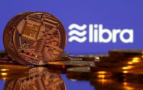 Đồng tiền mô phỏng tiền số đặt cạnhlogo Libra của Facebook. Ảnh: Reuters