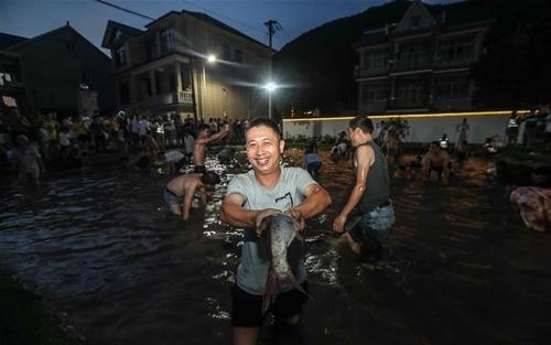 Du khách tham gia sự kiện bắt cá tại một ngôi làng ở Hàng Châu. Ảnh: Xinhua