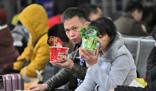 Hành khách Trung Quốc ăn mỳ gói trong khi chờ đợi. Ảnh: Imagine China