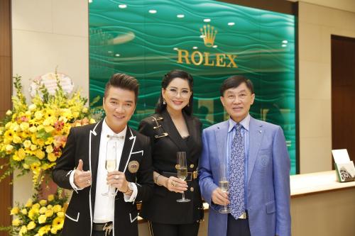 Ca sĩ Đàm Vĩnh Hưng cùng Chủ tịch IPPG – ông Johnathan Hạnh Nguyễn và Tổng giám đốc IPPG – bà Lê Hồng Thủy Tiên chụp ảnh lưu niệm trước bức tường kính xanh ngọc lục bảo đậm chất Rolex